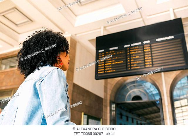 Young woman by arrival board in railway station