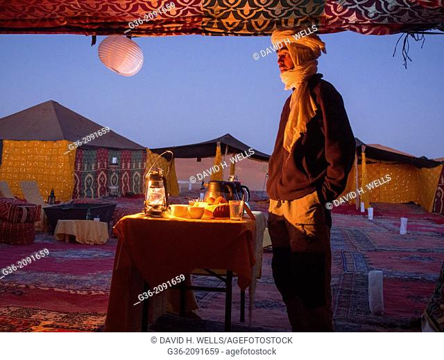 Man in winter clothing, making tea at tent in Erg Chebi, Morrocco