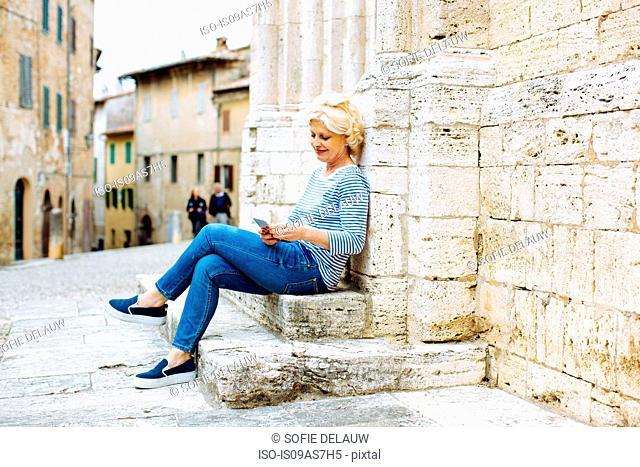 Mature woman looking at smartphone, Tuscany, Italy