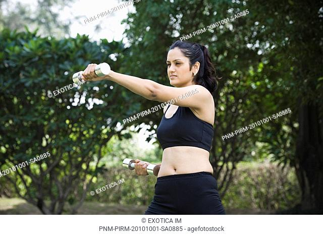 Woman exercising with dumbbells in a park