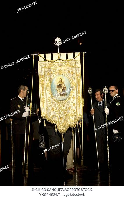 Town officials using ceremonial staffs walk behind a banner of the Virgen del Carmen inside a church during an Easter Holy Week procession in Prado del Rey