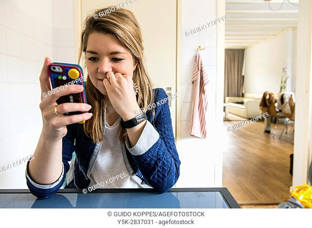 Tilburg, Netherlands. Young adult blonde girl admiring her published images on the photographers smartphone