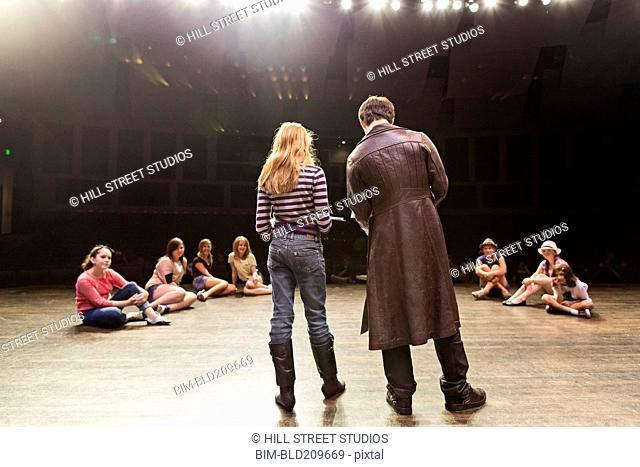 Students practicing lines on stage