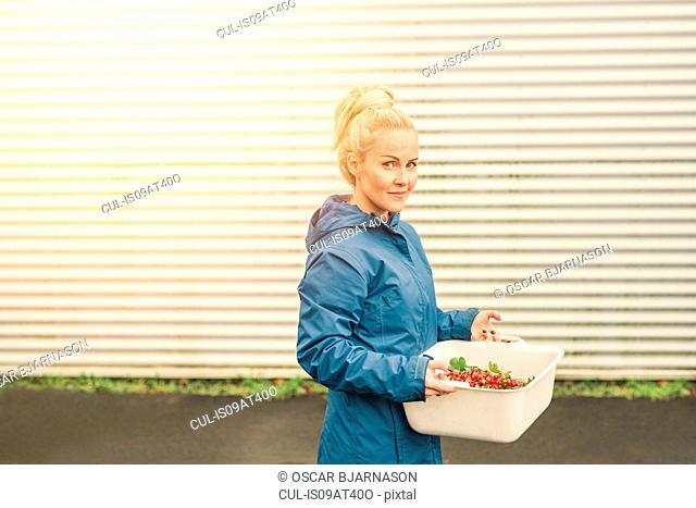 Mid adult woman holding container of redcurrants, outdoors