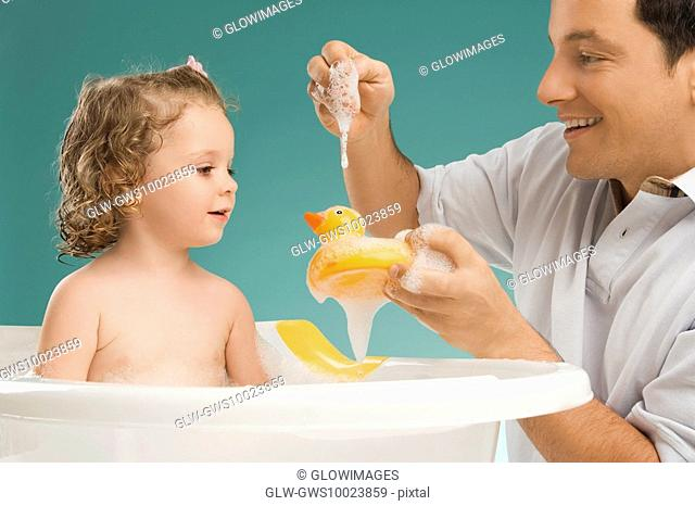 Mid adult man playing with his daughter and smiling
