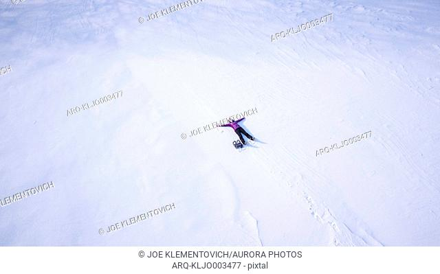 Aerial view of single woman making snow angel outdoors in winter