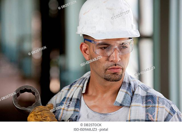 Mid adult construction worker wearing hard hat, looking away