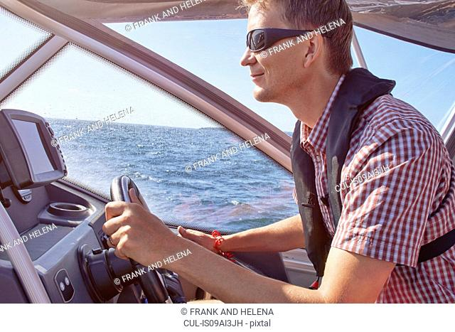 Mid adult male driving boat