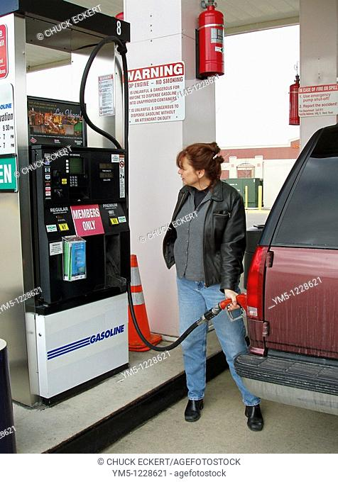Woman fueling an American gas guzzling Chevy Suburban SUV