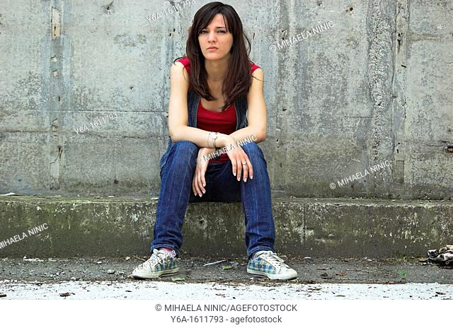 Portrait of a serious young woman looking at camera sitting in front of a cement wall