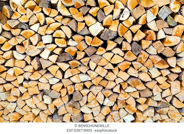 Pile of firewood as tree trunks storage for burning in winter
