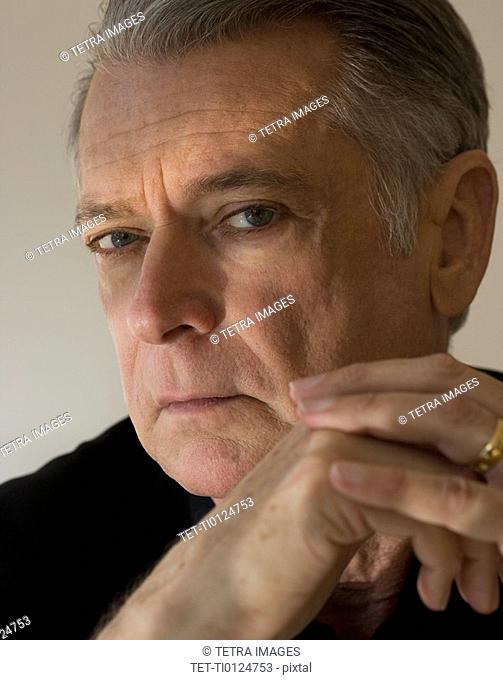 Senior man with hands clasped