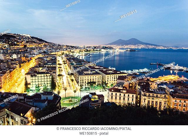 Naples, Campania, Italy. View of the bay by night and Mount Vesuvius Volcano in background