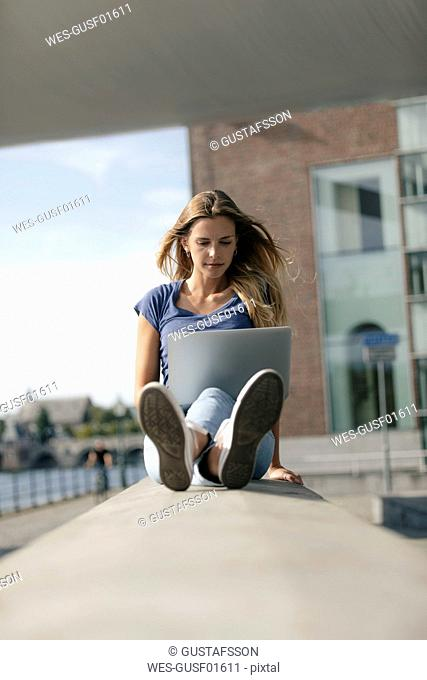 Netherlands, Maastricht, young woman sitting on a wall at the riverside using laptop