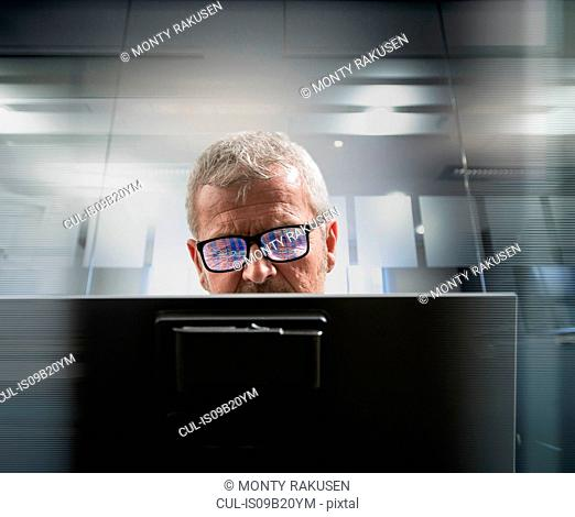Composite image of businessman at computer screen with graphical data reflected in glasses
