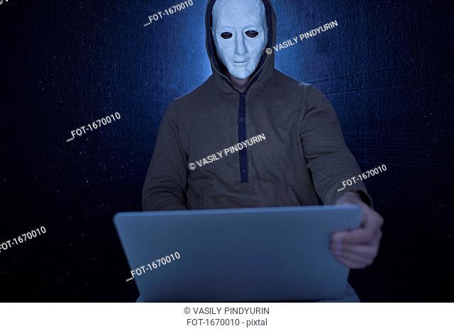 Computer hacker wearing mask using laptop against black background