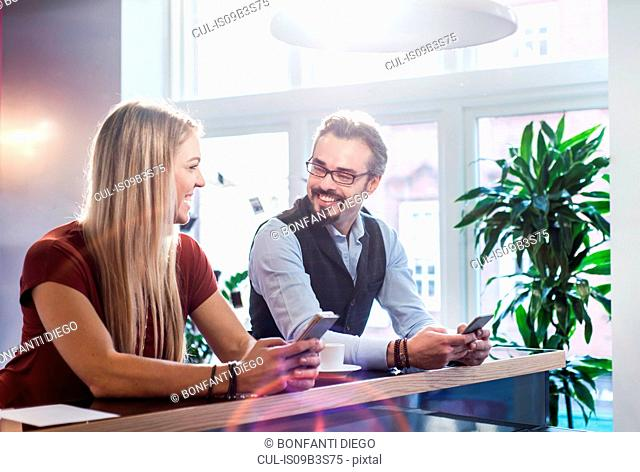 Businessman and woman chatting during coffee break in office