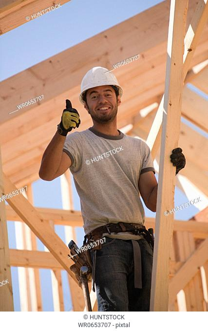 Carpenter showing thumbs up sign and smiling