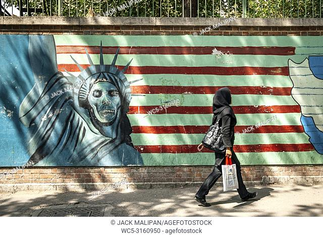 veiled muslim woman walking by anti american and israel propaganda mural on tehran street iran outside former US embassy