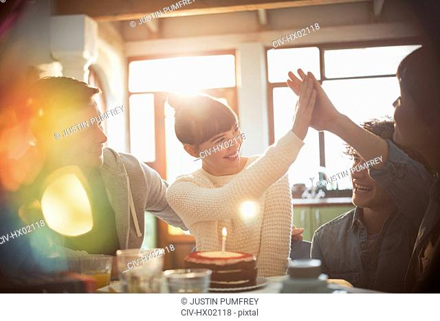 Young friends celebrating birthday with cake and candle high-fiving