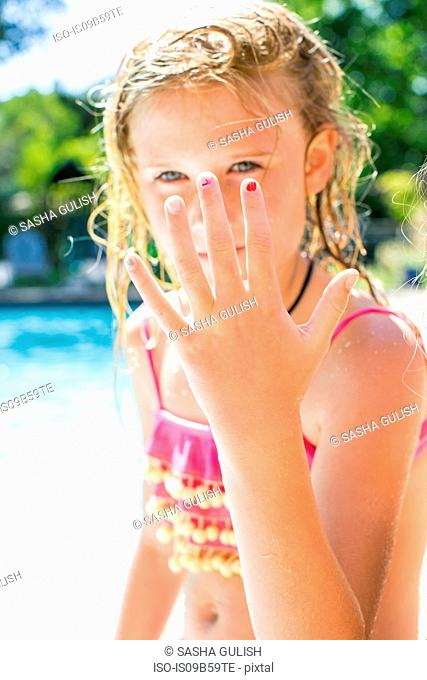 Portrait of girl holding up hand by swimming pool