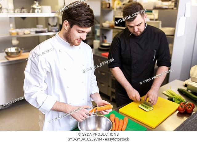 chef and cook cooking food at restaurant kitchen