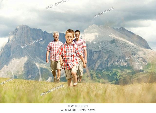 Italy, Seiseralm, Grandfather, Father and son 6-7 walking in meadow, smiling, portrait