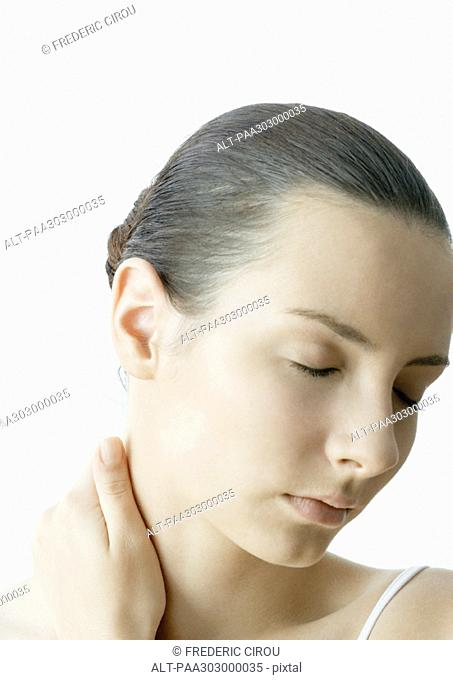 Woman with hand on neck and eyes closed