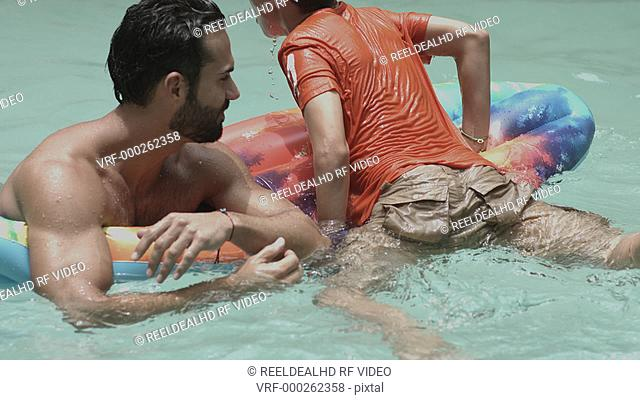 Father and son playing together in swimming pool having fun