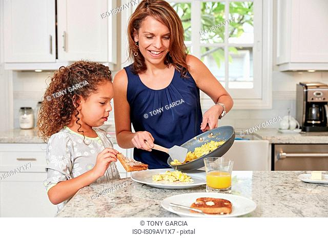 Mother at kitchen counter serving daughter scrambled eggs from frying pan