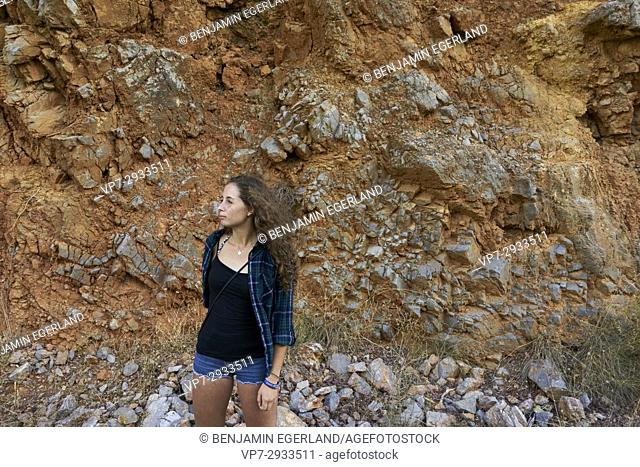 thoughtful British girl against red stone wall in mountains during travel adventure in Crete, Greece