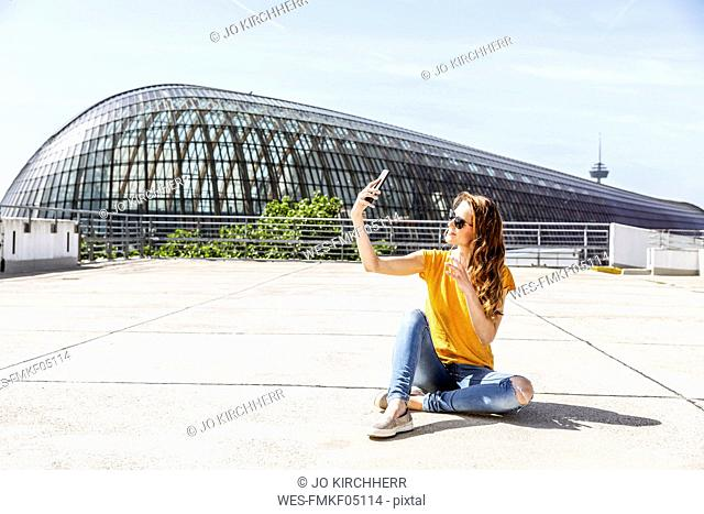 Germany, Cologne, smiling woman sitting on parking level taking selfie with smartphone
