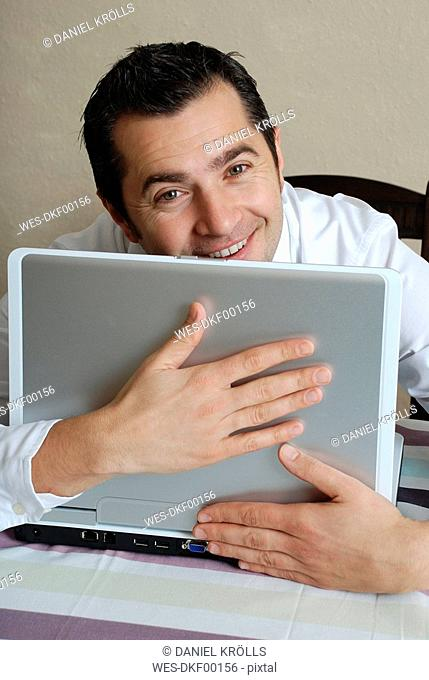 Young man with laptop, portrait