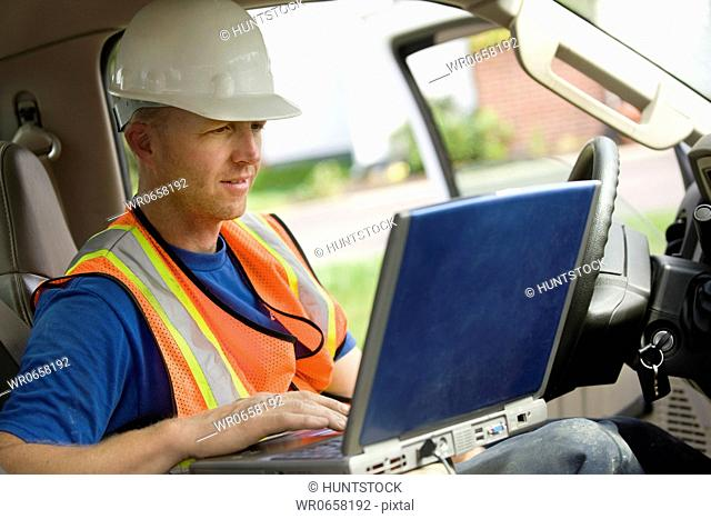 Construction worker using laptop in truck