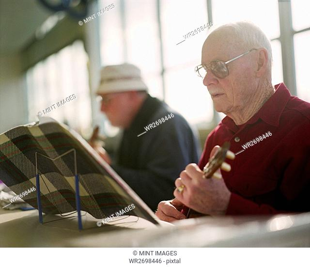 Two elderly men playing ukulele instruments in a senior center