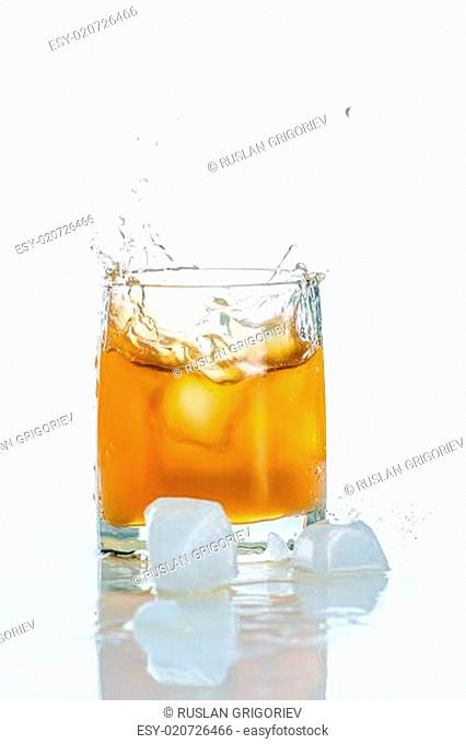 Apple juice in glass and Red juicy apple with green leaf on white background
