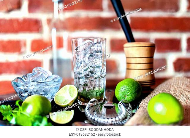 cocktail at bar, fresh alcoholic drink with limes and ice