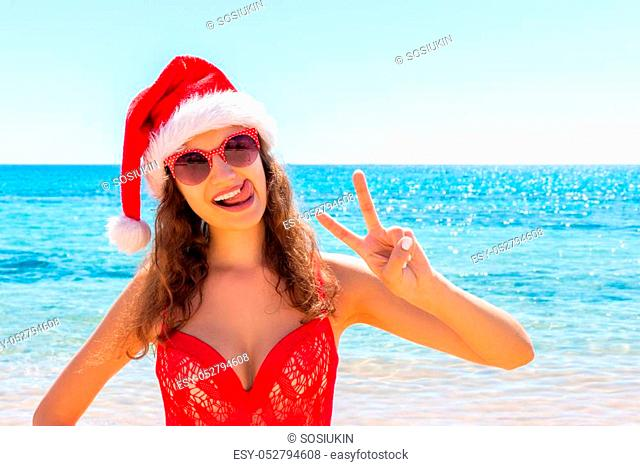 suntan young woman slim in santas hat and red bathing suit relaxing tropical sand beach. christmas winter vacation holiday concept