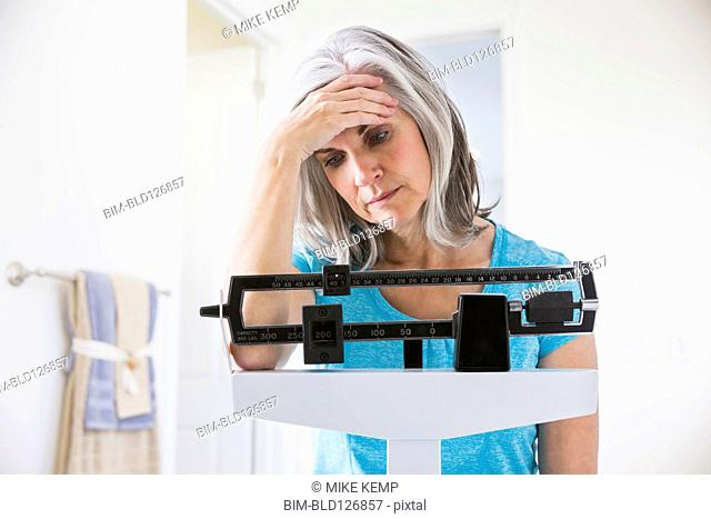 Unhappy Caucasian woman standing on weight scale