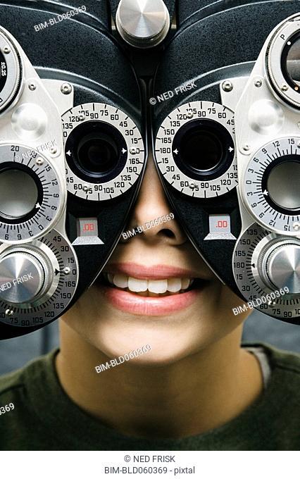 Asian boy having eyes examined