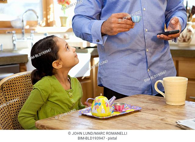 Father having tea party with daughter in kitchen