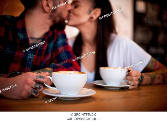 Couple kissing in cafe