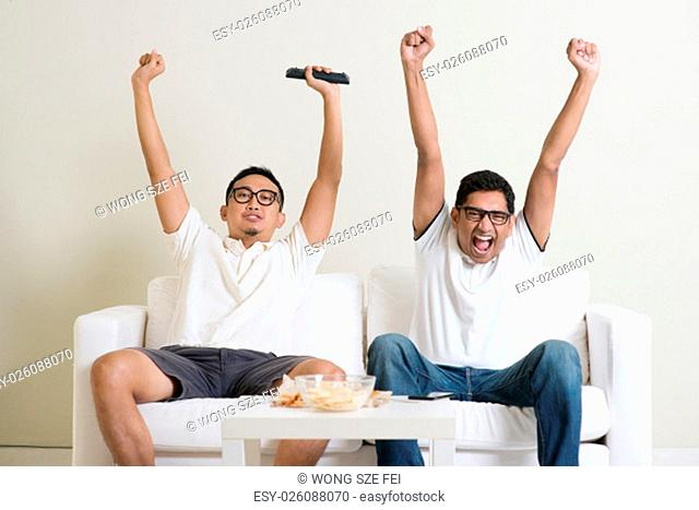 Friendship, technology and home concept. Happy male friends with remote control and junk food at home