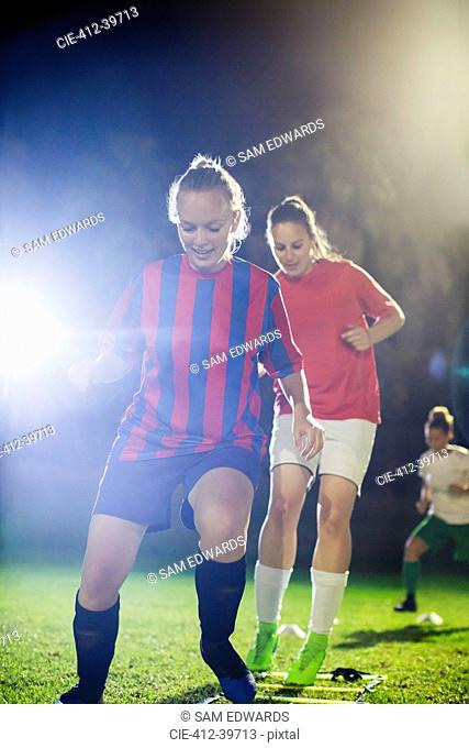 Young female soccer players practicing agility sports drill on field at night