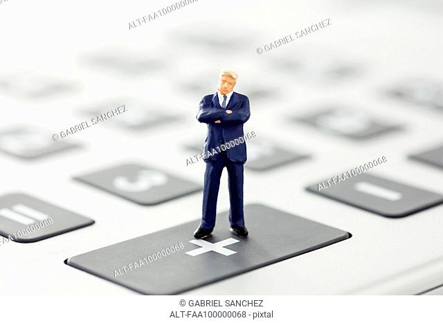 Businessman figurine standing on calculator