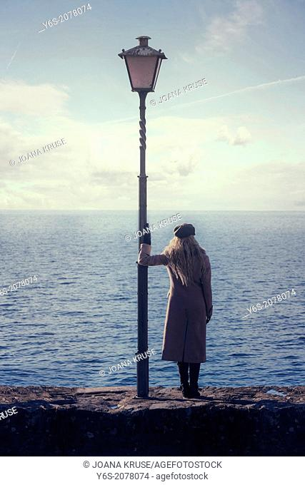 a woman in a pink coat is standing next to a lantern at the sea