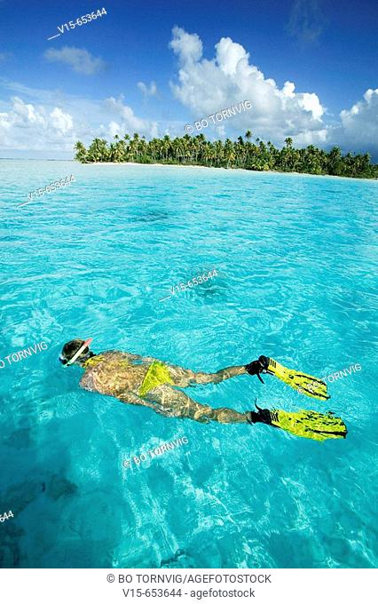 Girl snorkling in water on tropical island