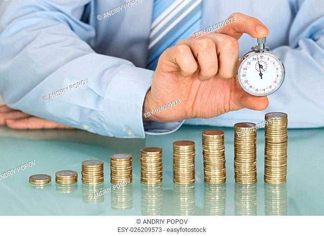 Close-up Of Businessman Holding Stopwatch In Front Of Stacked Coins