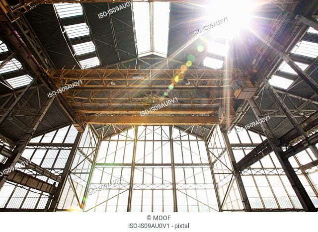 Low angle view shipyard building roof and gantry in sunlight
