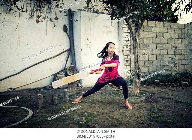 Mixed race girl playing cricket near wall